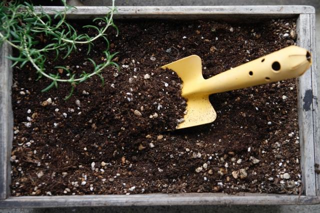 ショベルで土と肥料を混ぜる